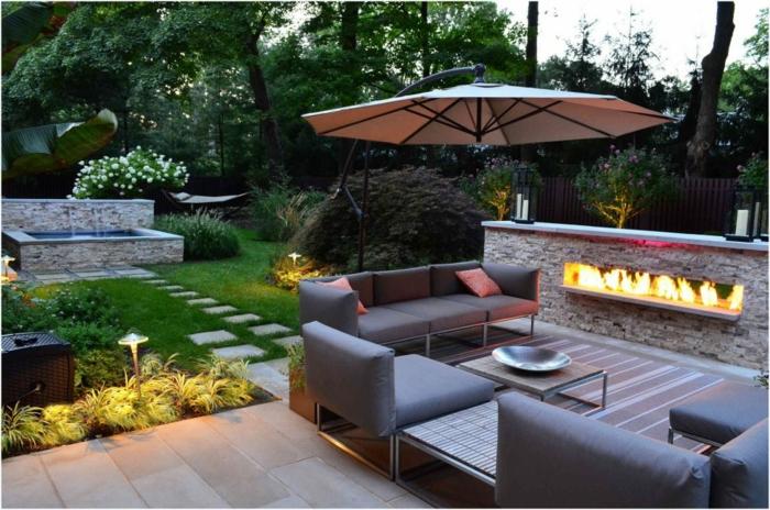 casa y jardin, patio con grande espacio para recreo, sillones y sofás modernos con lámpara tipo sombrilla y chimenea empotrada en la barra