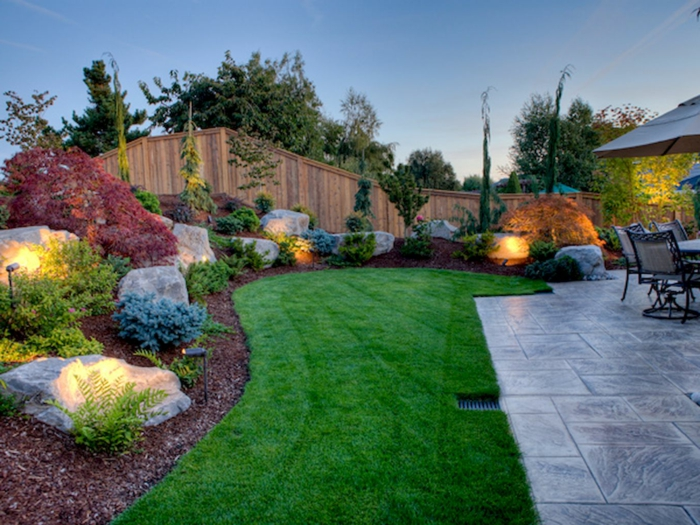casas con jardin, patio grande decorado con césped, piedras y lámparas decorativas, azulejos grises, patio de recreo