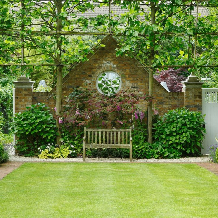 casa y jardin, propuesta para un jardín pequeño, cerca masiva de forma triangular y ventana oval, banco de madera