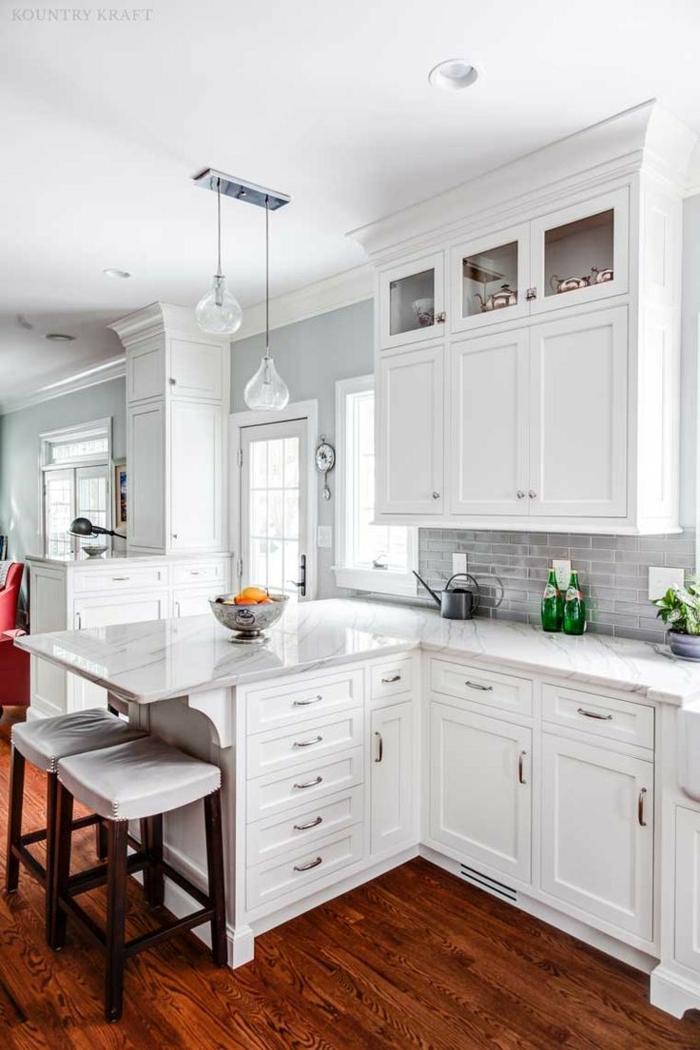 cocinas modernas blancas, cocina pequeña con barra, encimera de mármos, sillas altas tapizadas, muebles de madera, suelo con tarima