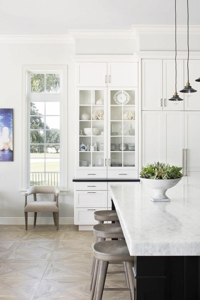 cocinas modernas blancas, cocina con suelo de baldosas, isla con encimera de mármol, lámparas colgantes, sillón y alacena con puertas de vidrio