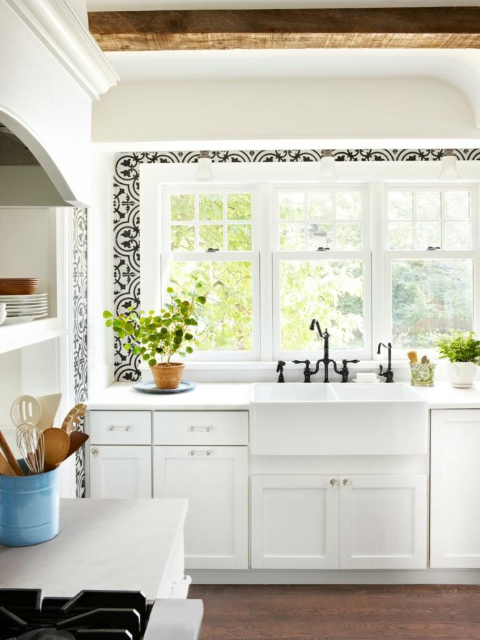 cocinas modernas blancas, cocina pequeña, fregadero blanco bajo ventanas, decoración con figuras negras, techo con vigas de madea