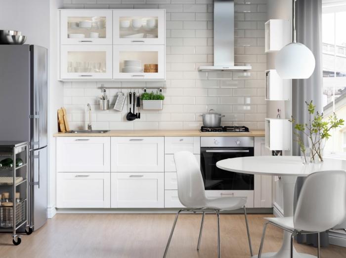 cocinas modernas blancas, cocina pequeña con comedor, mesa y sillas blancas de plástico, pared de ladrillo blanco