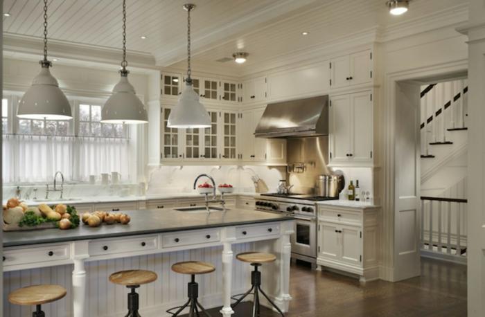 cocinas modernas blancas, cocina grande blanca, isla larga con fregadero, muebles de madera blanca, sillas de barra redondas, lámparas colgantes