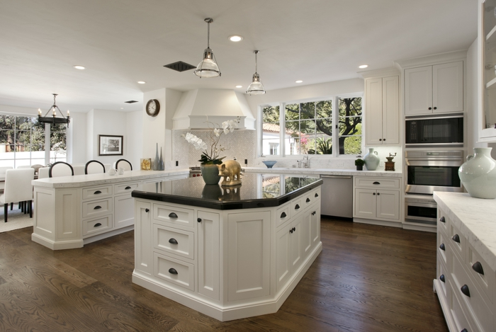 cocinas modernas, cocina grande con isla y barra, encimera de mármol negra, comedor con mesa larga