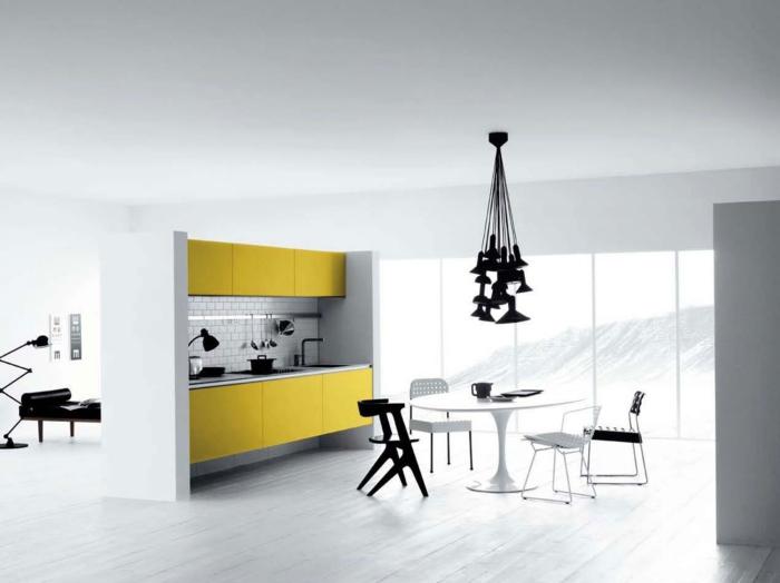decoracion cocinas, cocina moderna en blanco y amarillo con mesa redonda y sillas desparejas, ventanal y lámpara de araña negra