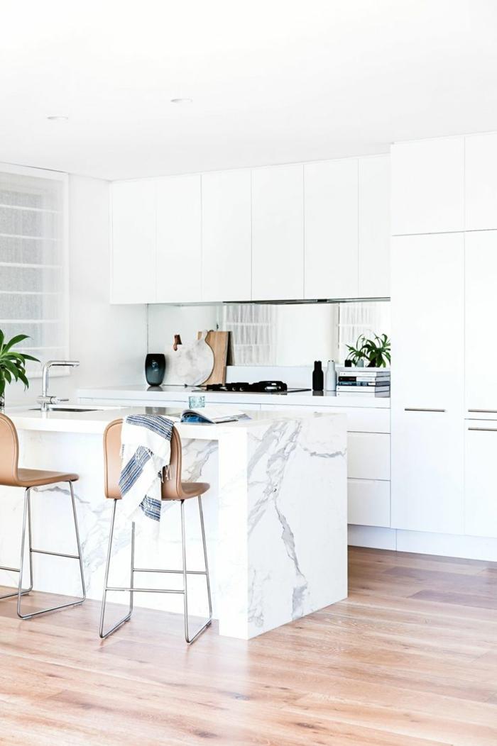 madera blanca, cocina moderna con isla de mármol con fregadero, suelo laminado, sillas altas color cobre