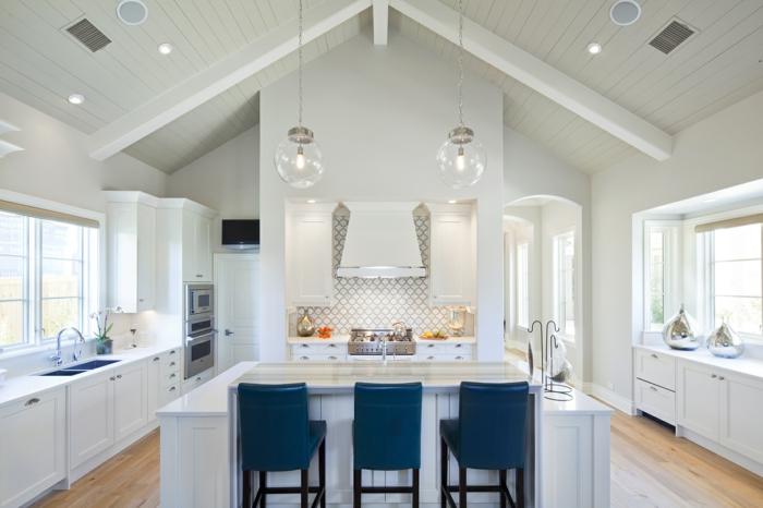 madera blanca, cocina con techo triangular, isla con sillas altas azules, muebles de madera bñanca, suelo laminado madera, mucha luz natural
