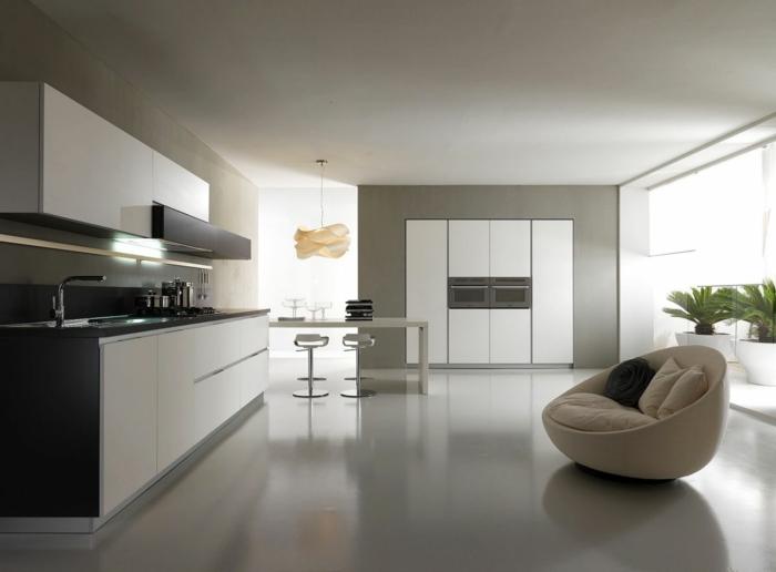 cocinas con isla, cocina moderna en blanco, negro y gris, barra con sillas altas, poca luz y sillón con cojines