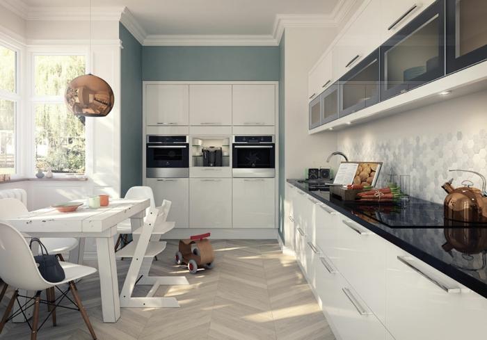 cocinas blancas, cocina blanca con comedor, encimera negra, dos hornos, suelo con parquet, pared azul, lámpara colgante cobriza, muebles altos con puertas de vidrio