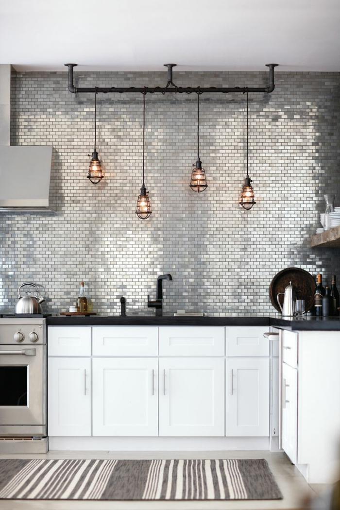 cocinas blancas, cocina pequeña estilo industrial, lámparas colgantes,pared con azulejos plateados, encimera y fregaero negros, tapete rayado