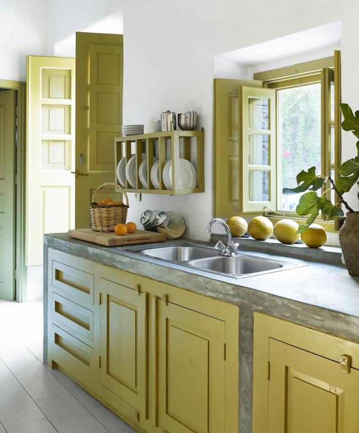 cocinas pequeñas alargadas, ejemplo de cocina con ventana y puerta a la terraza, muebles color ocre verde, estantes empotrados