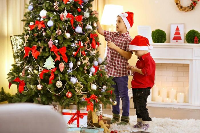 arbol de navidad decorado con cintas en moño rojas, pequeñas bolas y ornamentos en diferentes colores, corona de navidad en la pared