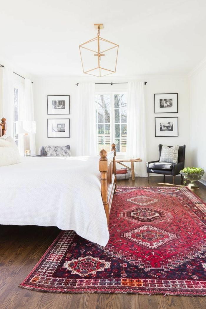 decoracion habitacion, dormitorio con ventanal y mucha luz, alfombra en tonos rojos, cama doble de madera, sillón negro
