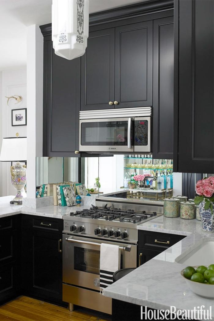 cocinas en l, grande armario en negro con microondas empotrado, suelo de parquet, lámpara con ornamentos