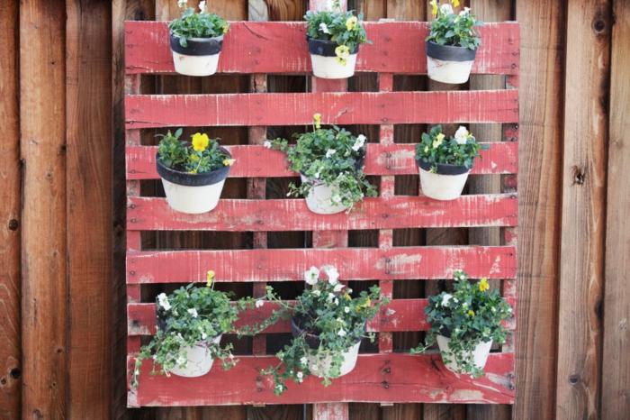decoracion de jarjines casera, palet pintado en rojo con efecto reusado, pequeñas macetas en blanco y negro con plantas