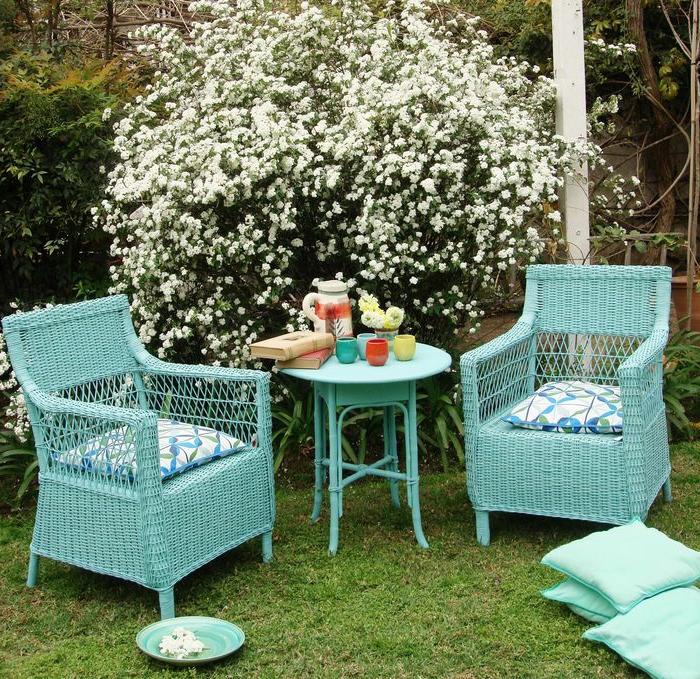 decoracion de jardines, muebles en color azul marino de madera, sillas de mimbre y mesa redonda, arbusto con pequeñas flores blancas