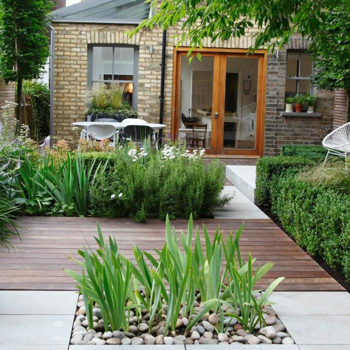 decoracion de jardines, bonito patio pequeño con parquet y parceles con plantas y piedras decorativas, casa estilo rústico
