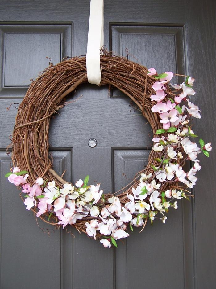 guirnaldas navideñas, corona de navidad de ramas secas y flores rosadas, cinta blanca, puerta de madera