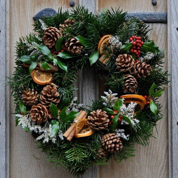 guirnaldas navideñas, corona natural verde de ramas de pino con canela, rodajas de naranja, bayas rojas