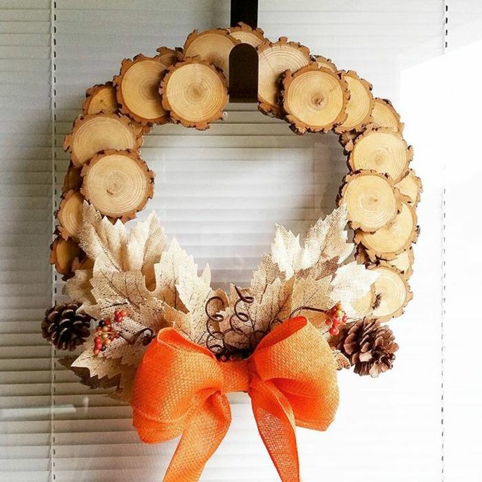 guirnaldas navideñas, guirnalda de trozos de madera redondos con hojas otoñales y lazo de cinta naranjada