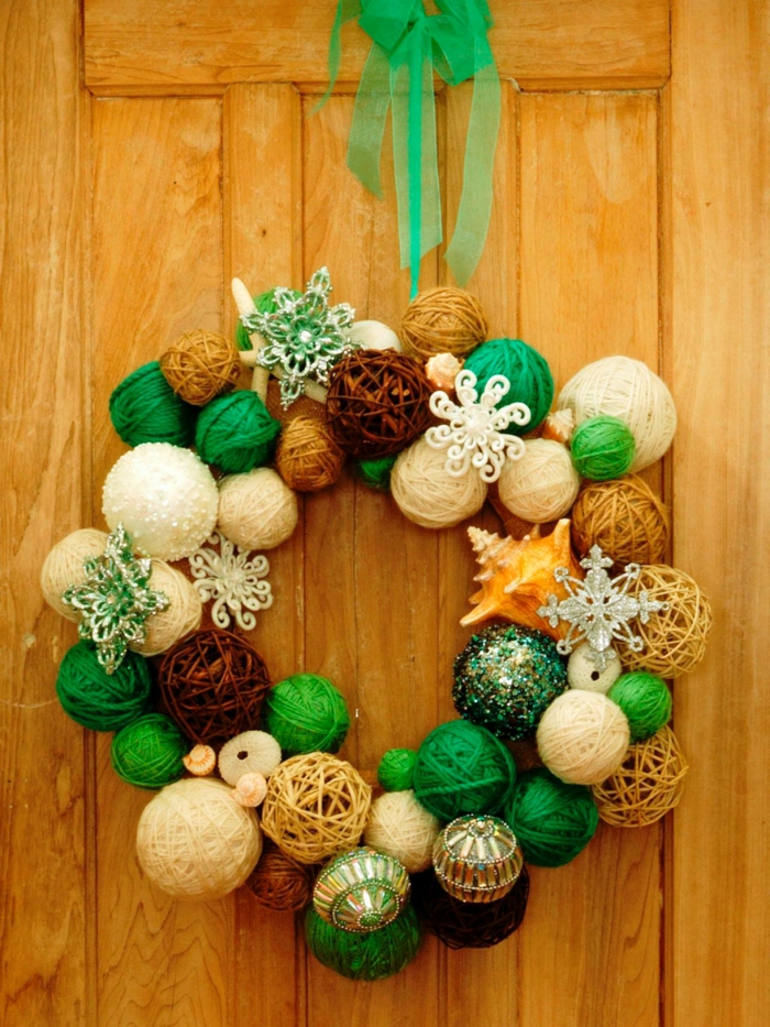guirnaldas navideñas, puerta de madera con corona de navidad hecha con bolas de hilo en verde, marrón y beige, concha y copos de nieve