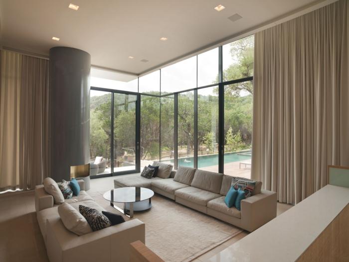 salon moderno, sala de estar espaciosa con vista a la piscina, grandes sofás en color avellana, cortinas masivas y largas en beige