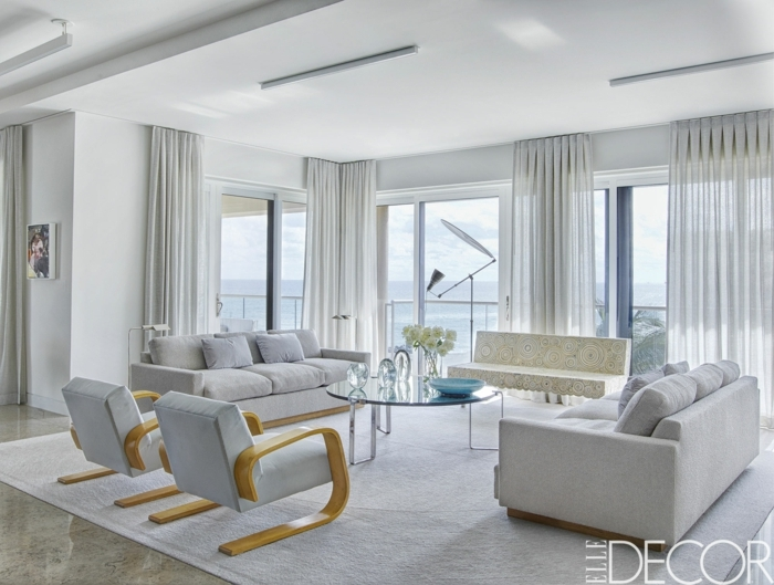 tipos de cortinas, visillos efímeros que están muy de moda, vasto salón en tonos claros y naturales, mesa de vidrio redonda