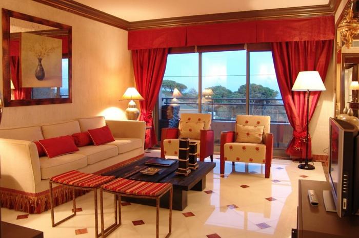cortinas modernas, color rojo vivo, cortinas con guardamalleta recta, grande sofá de beige claro, pequeñas sillas modernas, mesa de madera baja