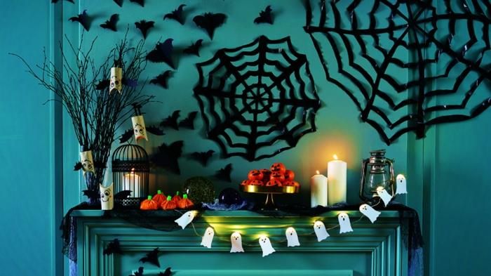 ideas para halloween, propuesta fácil para decorar las paredes, adornos en formas de telarañas grandes, pequeños murciélagos, guirnaldas de fantasmas pequeños, velas decorativas