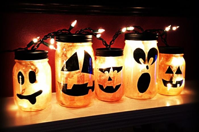 manualidades caseros, frascos con caras pintadas en negro, bombillas y velas,puestos en un estante de madera