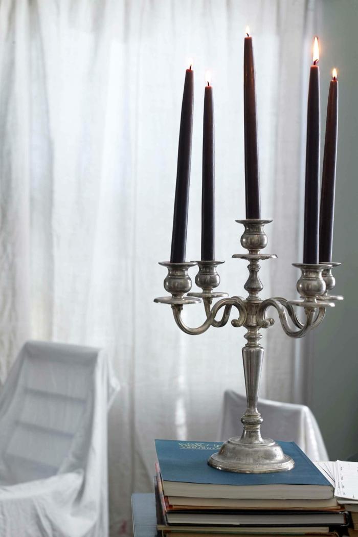 ideas para halloween, velas grandes en negro, candelero masivo vintage de plata, cortinas blancas, muebles cubiertos de sábanas