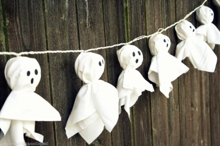 manualidades halloween, guirnalda de fantasmas colgadas en un hilo, figuras de tela blanca, decoración casera muy fácil