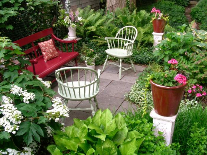 como hacer un jardín en un terreno pequeño, banco rojo de madera con sillas blancas vintage, macetas con geranios, muchos arbustos de diferente tipo