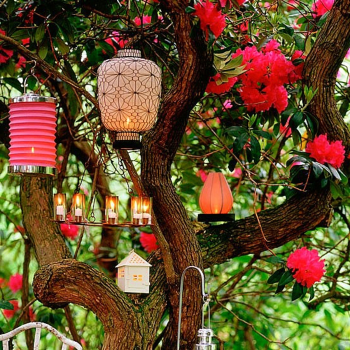 como hacer un jardín, lámparas bonitas de diseño y tamaño diferente, colgadas en el árbol de flores rojas