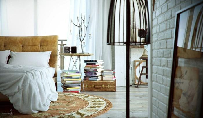 dormitorios de matrimonio, dormitorio con cama doble y tapete redondo, libros sobre maleta antigua, pared de ladrillo blanco