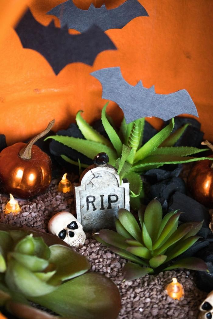 manualidades halloween, calaveras, plantas artificiales, calabazas doradas y formas de murciélagos dentro de una calabaza decorativa de halloween