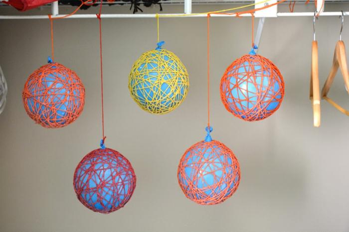 manualidades halloween, bolas colgantes en color rojo, amarillo y naranja, globos para la preparación de la manualidad