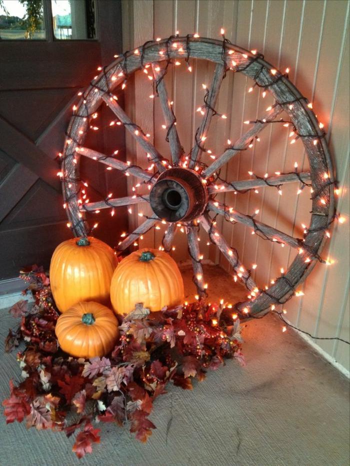 manualidades halloween, rueda de carroza con lámparas decorativas, tres calabazas y hojas de otoño en rojo