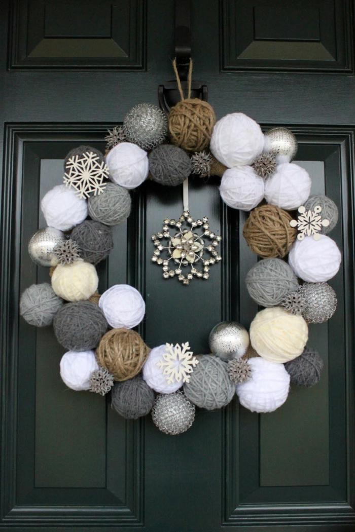 guirnaldas de navidad, puerta negra, corona de navidad con bolas de hilo gris, blanco y marrón, copos de nieve falsos