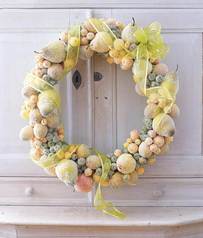 guirnaldas de navidad, corona amarilla de navidad con frutas, peras, bayas y manzanas cubiertas de escarcha con cinta decorativa