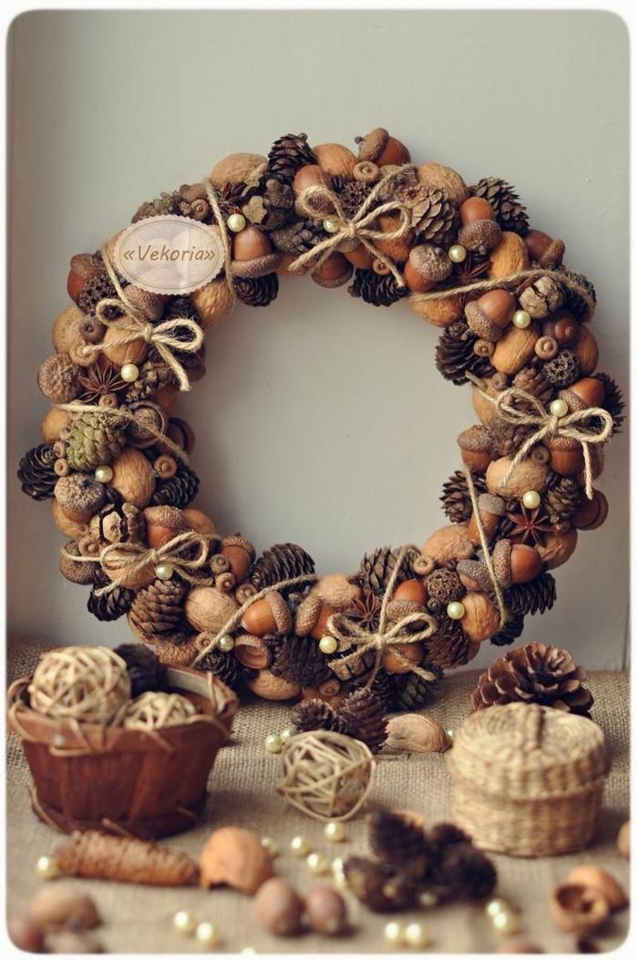 guirnaldas de navidad, corona navideña marrón con bellotas y nueces, lazos beige y piñas naturales