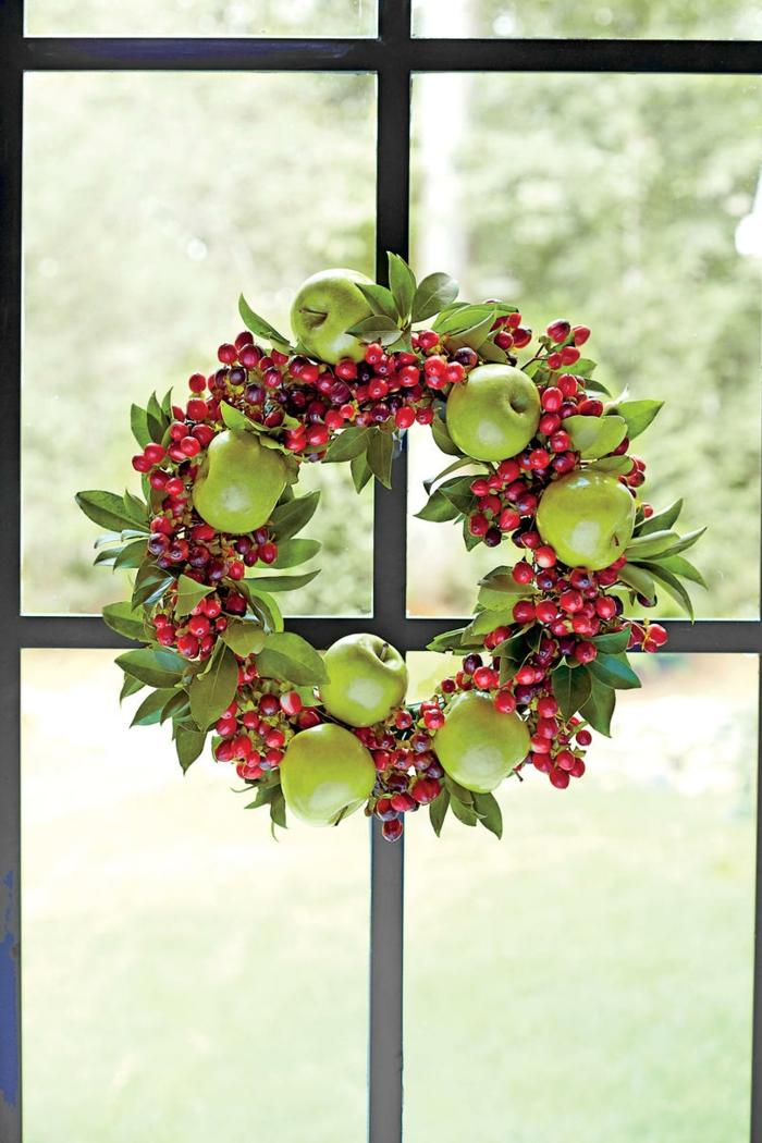 guirnaldas de navidad, corona de navidad de hojas verdes, manzanas y muerdago rojo, ventana con marco negro