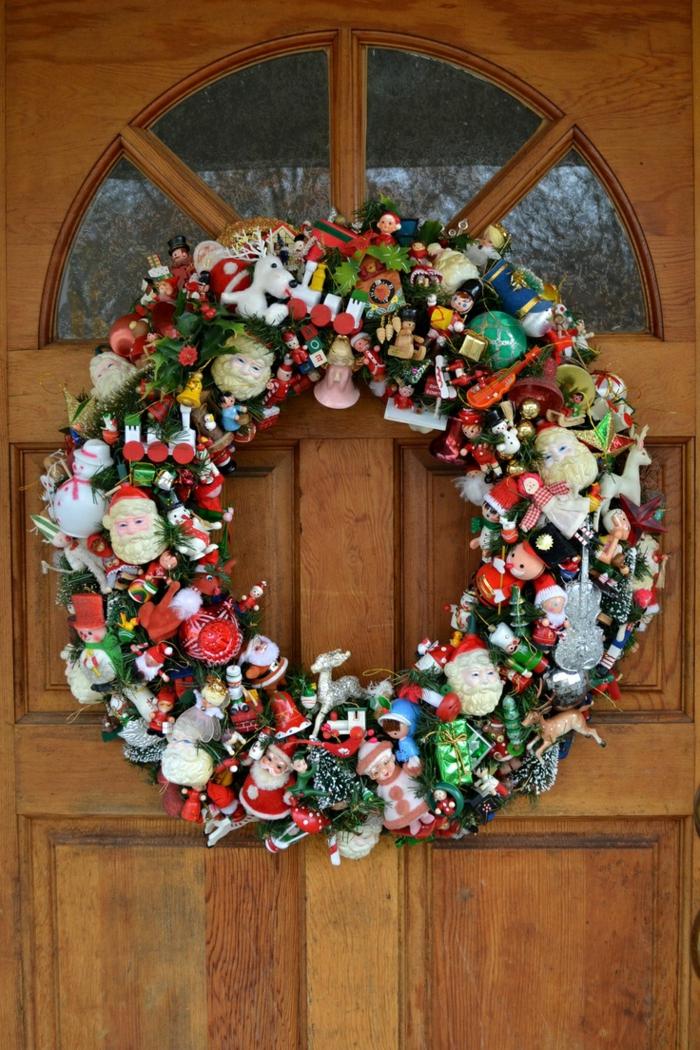guirnaldas de navidad, corona de navidad en puerta de madera, base verde con muchos adornos, papa noel, enanos, juguetes