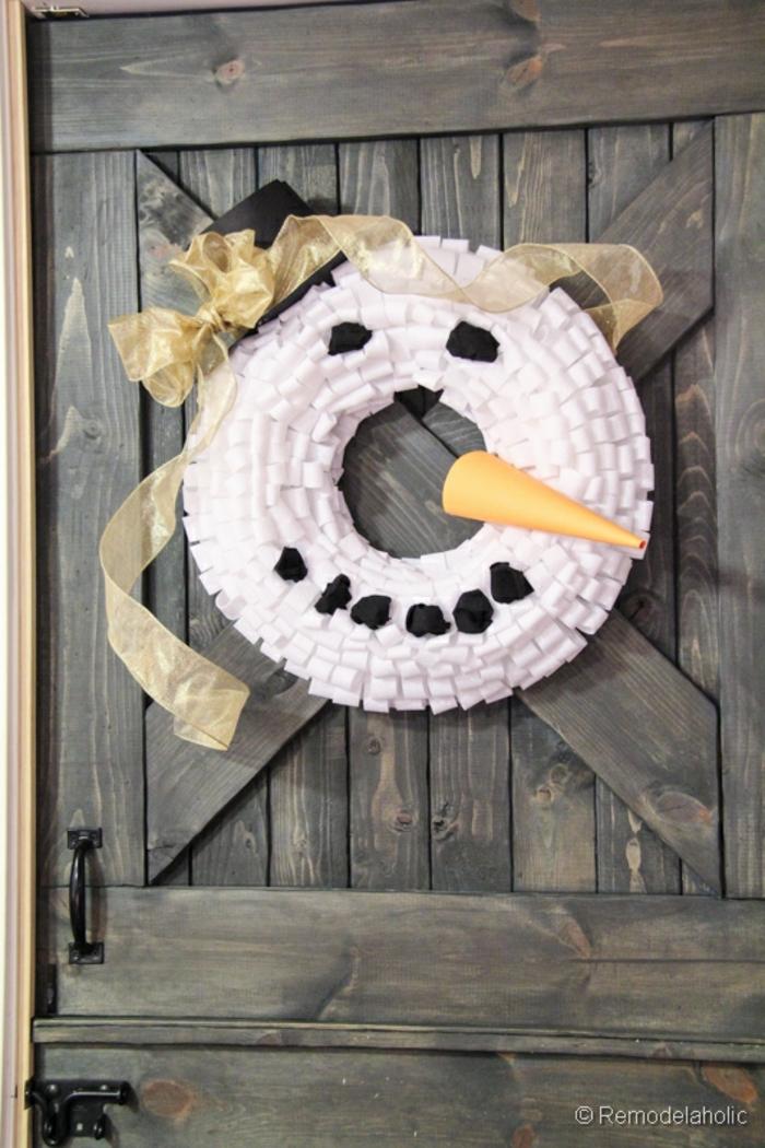 manualidades navidad, corona de navidad con cara de muñeco de niece, gorro negro con cinta dorada, puerta rústica
