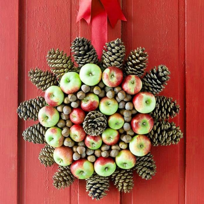 manualidades navidad, corona navideña natural de manzanas y piñas de pino, puerta de madera roja
