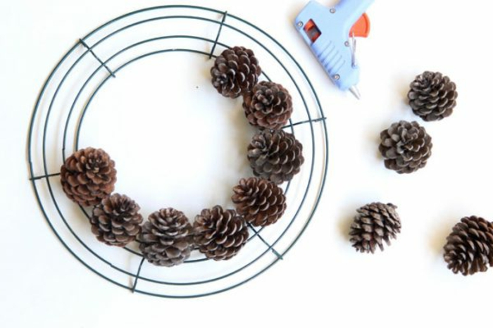 manualidades navidad, cuerda circular de metal, piñas naturales, pistola encoladora, tutorial para hacer corona navideña en casa