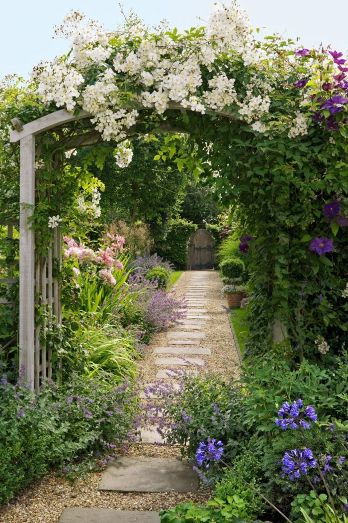 diseño de jardines, bonita bóveda con plantas enredaderas en blanco y lila, sendero con pavimento de piedras, seto vivo alto, jardín con toque salvaje
