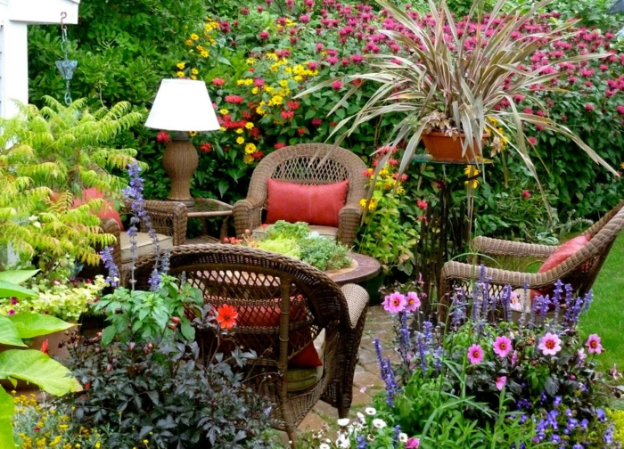 como hacer un jardin, ejemplo de rincón amueblado en el patio, sillas de mimbre marrón, lampara vintage, muchas plantas y flores