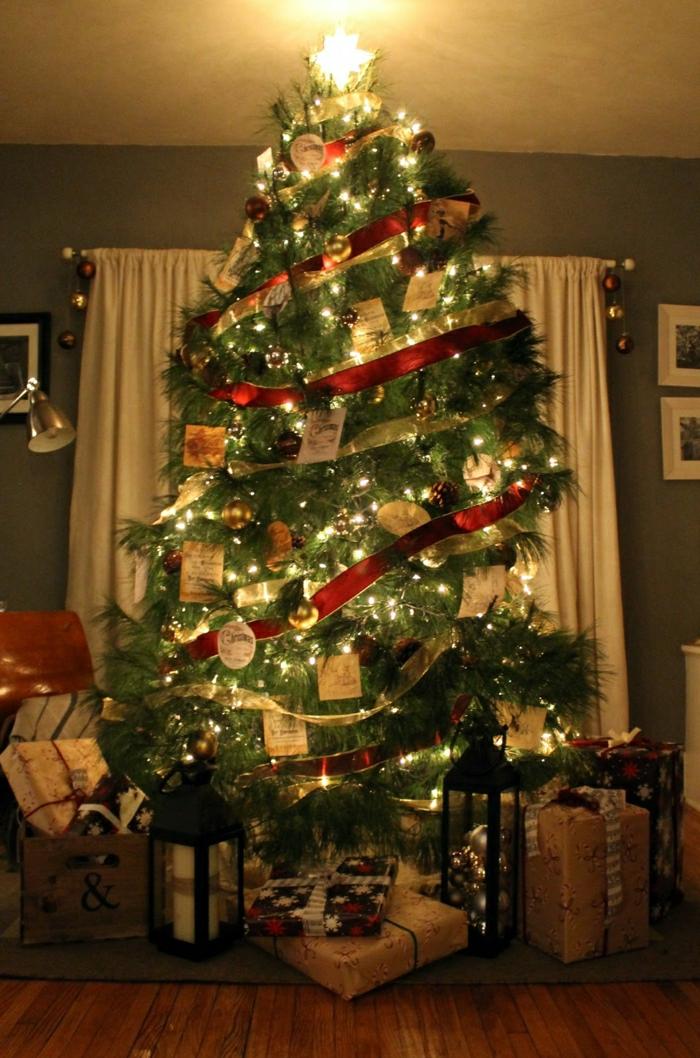arbol navidad tradicional con adornos en rojo y dorado y grandes cintas envueltas al árbol como guirnaldas